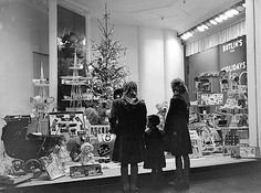 §§§ : The main shops in Oxford street lit up with Christmas lights . Three youngsters looking in Selfridges window : 1949