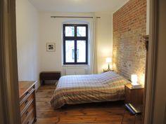 Einfach eingerichtetes Schlafzimmer mit Backsteinwand und schönen Holzmöbeln in Berlin #Schlafzimmer #Backstein #Berlin