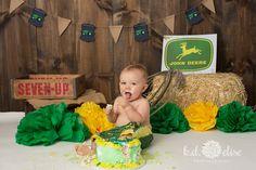 Baby eating cake during John Deere themed first birthday cake smash.