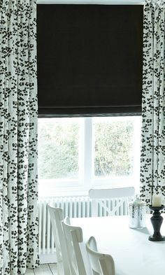 Add a touch of monochrome into your home with striking plain Roman blinds and patterned Curtains.