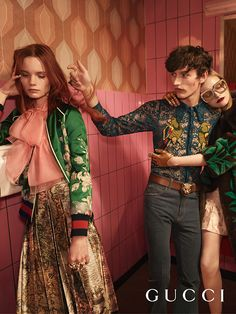 Model Polina Oganicheva in a silk duchesse embroidered bomber with Web trim, pink coral silk organdy top, printed silk duchesse pleated skirt. Arnis Cielava in a lace shirt with parrot embroideries, a leather belt with a tiger head buckle, blue washed denim high waist pants. Mia Gruenwald in a plush jacket with green leaf intarsia, taffeta jacquard bermuda with ruffle detail, square eyewear with gold crystals and metal interlocking GG on the temples.