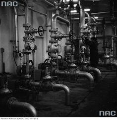 Pracownik reguluje zawory instalacji fabrycznych.