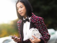 A printed blazer is paired with a white blouse, a bow-tie and statement purse.