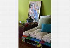 Ao lado do sofá, a bobina de madeira pintada de azul atua como mesa lateral. Casa do arquiteto Mauricio Karam