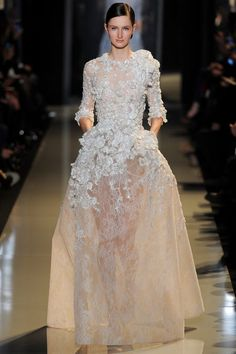 SPRING 2013 COUTURE  Elie Saab /   What was signature Saab, of course, was the beadwork, this time rendered in tone-on-tone or silvery embroideries on lace and tulle of varying transparencies. An Ode to Delicateness, he called the collection, and, indeed, with illusion necklines and sheer sleeves, his creations at times seemed to float on the body.