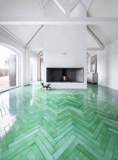 Os ambientes grandes também merecem cor. Essa sala de estar com lareira, por exemplo, recebeu azulejos esverdeados e brilhantes.