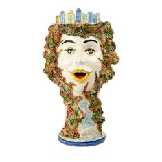 This large flower pot was achieved using a combination of a lathe, and hand modeling of the details. Depicted on the vase is a woman's face surrounded by various plants. The woman's head supports the skyline of the city of New York.