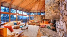 Wood, stone and glass round out this living room with high ceilings and custom built furniture