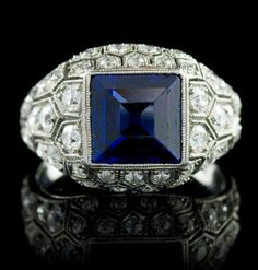 An Art Deco Platinum, Sapphire and Diamond Ring, J.E. Caldwell  Co., containing one square step cut sapphire measuring approximately 7.60 x 7.50 x 4.60 mm and numerous old European cut diamonds weighing approximately 0.90 carat total within an openwork setting with millegrain accents. Stamp: JECCo G4800.