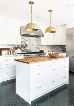white kitchen with marble backsplash and tiled floor