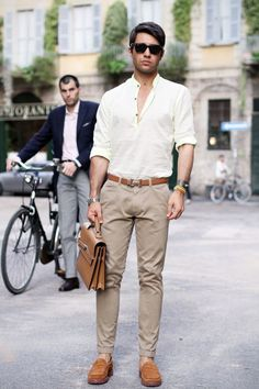 Shop this look on Lookastic:  https://lookastic.com/men/looks/henley-shirt-chinos-loafers-briefcase-belt-sunglasses-watch/10624  — Black Sunglasses  — Beige Henley Shirt  — Brown Leather Belt  — Silver Watch  — Tan Leather Briefcase  — Beige Chinos  — Tan Suede Loafers