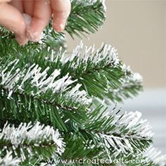 Learn how to add a touch of snow to your artificial tree in two simple steps!