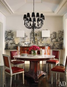 In the dining room, a tole chandelier from Laurin Copen Antiques is paired with Jansen chairs and a vintage Ralph Lauren Home marble-top pedestal table. Zuber's Les Lointains wallpaper lines the room; the wide-plank floor is stained in Sydney Harbour Paint's Palm Beach Black.