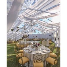 Modern outdoor wedding with chandeliers - the yellow cushions bring a pop of color to a white wedding ~ Amber Event Production