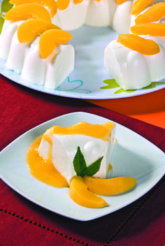 Gelatina de yogurth natural, servida con salsa de mango y trocitos de mango y hojitas de menta