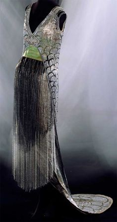 """Evening dress, Gustave Beer, Paris, 1919. Black silk tulle with silver bead and rhinestone embroidery, silver bead fringes, long train, sash in green and gold stripes, silver lamé under dress. The scale or """"seigaiha"""" (blue ocean waves) pattern seen on this dress was used repeatedly in the 1920s. It was a popular motif of the Art Deco school. Kyoto Costume Institute."""