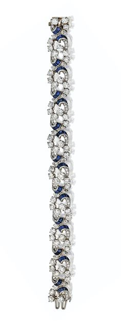 DIAMOND AND SAPPHIRE BRACELET, CIRCA 1950.  Designed as a series of stylized floral clusters and ribbons, set with 81 round diamonds weighing approximately 25.75 carats, 72 small round diamonds weighing approximately 1.40 carats and  72 calibré-cut sapphires, mounted in platinum, length 8 inches, trademark McT for McTeigue.