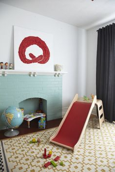 Modern playroom in primary colors that don't feel primary.  Love the painted fireplace, red slide, modern art, and yellow Alvine Ruta rug from Ikea.