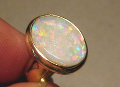 3 cwt Solid White Opal Ring Heavy 14k Gold -  Beautiful Large White Opal Ring that is much brighter in person.   Solid 14k Yellow Gold Ring with one Coober Pedy White Opal.     OPAL WEIGHT:  Approx 3.0 cwt COLORS:  Red & Blue PATTERN:  Small Patch QUALITY:  Flawless BRIGHTNESS:  3 GOLD WEIGHT:  8 grams 14k Yellow Gold SETTING:  16.7 mm across on the top deck RING SIZE:  USA Size 7 or British / Australian size N 1/2