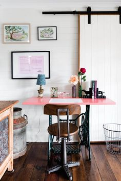 Singer sewing table converted into an office desk decorated with flowers, books and a small lamp. A sliding barn door separates the main living area from the bedrooms | Photography: Hannah Puechmarin Singer Table, Singer Sewing Tables, Table Desk, Dining Table, Bedroom Photography, Library Bookshelves, Small Lamps, Home Office Organization, Vintage Country