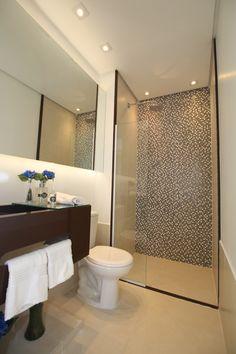 Este banheiro todo em tons neutros, porém com um destaque no mármore marrom escuro da bancada e uma parede ao fundo em pastilha.  Projeto e fotografia da arquiteta Pricila Dalzochio.