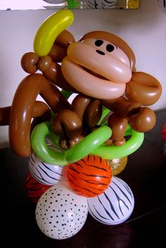Balloon animal print rounds combined w/ silly monkey holding a banana creates a fun 18-in table topper. www.HollyNagel.com #funballoonart #balloondecor #balloons