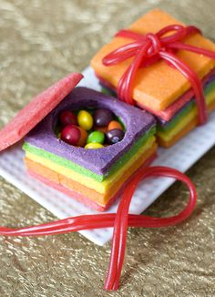 "Bake dyed sugar #cookies, cut out circles in the centers of the cookies, stack the cookie cut-outs together on top of a whole cookie, fill with the #candy of your choice, and top with another whole cookie! Use other candies (twizzlers are an easy option) to ""wrap"" the cookie gifts. Really cute surprise at parties."