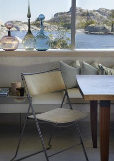 A beautiful view of the sea just outside the window at this Kristiansand summerhouse by Heiberg Cummings. The light filtering through the coloured glass bottles lends a magical touch