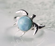 Sea turtle ring with genuine larimar gemstone features an adorable sea turtle which was hand carved, then cast in .925 sterling silver. The larimar is beautiful as the turtle shell and reflects turquoise aqua and sky blues, just like the colors of the Caribbean sea and sky. Ive worked with various organizations here in the Caribbean focusing on sea turtle conservation, and these beautiful, mystical beings have inspired me in ways I cant even begin to explain. They have changed my life for…
