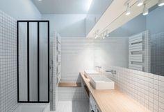Minimalista e funzionale, il bagno di questo loft di Parigi è rivestito da piastrelle quadrate bianche. Il mobile del doppio lavandino è in legno di rovere ed è stato disegnato su misura dai progettisti. Foto di: Maris Mezulis