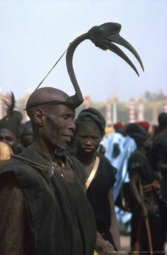 Hornbill Headgear Nigeria, Kaduna, Grand Durbar festival parade. 'A Northern Nigerian Hunter - The native hunter all over Africa is an adept in the art of stalking game for when armed with a weapon having but a short range, he must get near enough to his quarry to make his shot certain. In some parts of Northern Nigeria wooden head-dresses with horns like those of the antelope are worn. Here a Nupe is wearing one resembling a hornbill'