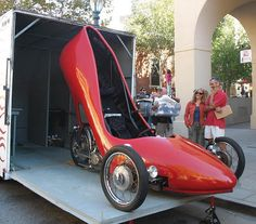 HERE'S A RED HIGH HEEL SHOE CAR FOR HER BECAUSE A MAN WOULDN'T BE CAUGHT DEAD IN THAT.