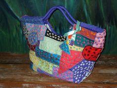 Bolsa de retalhos sobrepostos com contornos bordados em ponto caseado.