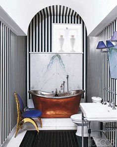Chic and graphic stripes painted on the bathroom walls at a couple's apartment in Paris draw the eye upward to the rounded arch