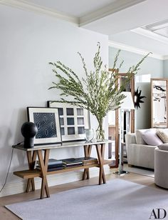 In the entry area, a vintage André Borderie table lamp mingles with artworks by Raoul Dufy (left) and Iran do Espírito Santo atop an Antonio Citterio console for Hermès   archdigest.com