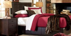 This rustic bedroom from Wayfair Canada features dark wood furniture, a red bedspread, and a fur throw, giving it a cozy winter cabin feel.