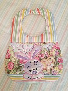 This bib has a cute bunny applique on it.This design is an ITH in the hoop machine embroidery design. The quilting is done in the hoop as well.The design comes in two sizes that fit the and hoops. Machine Embroidery Applique, Embroidery Patterns, Baby Bibs Patterns, Bib Pattern, Bunny Toys, Cute Bunny, Applique Designs, Gift Bags, Quilts