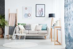 Paintings of cactus and hexagons hanging over a cozy sofa with many pillows standing next to a black lamp in living room interior Cozy Sofa, Blue Curtains, Diy House Projects, Simple Projects, Diy Home Improvement, Autocad, Living Room Interior, Decorating Your Home, Mid-century Modern