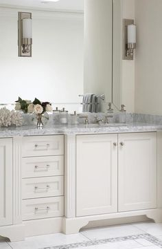 Sophisticated bathroom features a white vanity topped with carrara marble fitted with an oval sink under beveled vanity mirror illuminated by polished nickel and white glass sconces.