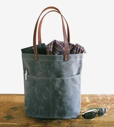 This handcrafted wax canvas tote bag is ready to be carted betwixt farmers markets and the office, and has plenty of room (and pockets on the front) to bring all of the essentials along for the ride.