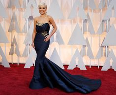 Photograph: Mario Anzuoni/Reuters One of the star performers of the night, singer Rita Ora's deep blue off-shouldered gown and its train were all kinds of dreamy.  JLo, Dakota Johnson, Rita Ora: Oscars' HOTTEST red carpet styles - Rediff.com