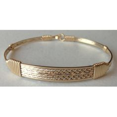 A great look and feel with 3 side stands with a middle accented by Mirrored Silver wire, four Diamond cut gold and two flat.  Stands out when grouped with other bracelets.  Great accent piece.