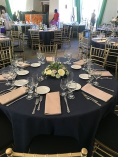 Navy linens, gold chiavari chairs, blush dupionique napkins. Plated meal place setting.