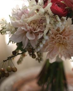 I don't know their season or how much they  cost but Dahlias would look very lovely in bouquets as well