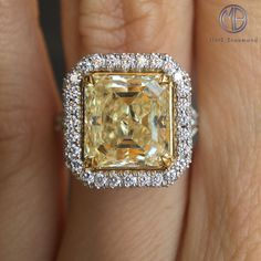 This magnificent canary yellow diamond engagement ring is such a stunner! This one of a kind masterpiece features a beautiful 5.02ct square step cut diamond. It is GIA certified at Z-VS1. It is exceptionally rare to find step cut diamonds with such a vibrant and beautiful fancy yellow color. The diamond has excellent clarity as well. This spectacular five carat gem is poised in the center of this handcrafted setting featuring a halo of round diamonds and a row set on the sides of the halo.