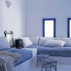 Dans un salon grec, les tours des fenêtres ont été peints en bleu rehaussé d'une frise. Les canapés maçonnés sont équipés d'épais matelas recouverts de tissu rayé bleu et de coussins blancs.