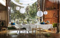 Eine lange Tafel aus LINNMON Tischen in Grau mit Wildblumen, Zitronen und frische weiße Tischdecken sind ideal für eine zünftige Sommerparty.