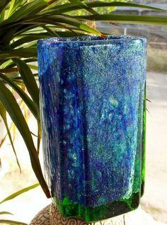 """Grønnblå vase fra den tiden Motzfeldt arbeidet ved Randsfjord og Plus samtidig. Meget god stand. H.17,5 cm, dm ca 10 cm 1,3 kg, tung. """"Benny Motzfeldts mangfoldige og frodige glasskunst innledet i slutten av 1960-årene en ny æra i norsk glasshistorie. Hun var den første i Norge til å bruke glass som medium for fri kunstnerisk utfoldelse."""""""