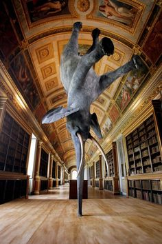 French contemporary artist Daniel Firman. Exhibited back in 2008, this life-size piece was seen at the Fontainebleau Castle in Paris, France. Called Wursa, the sculpture is balancing on its trunk 18,000 km above the earth. Firman consulted with a professional taxidermist to construct this piece making it look as real as possible.