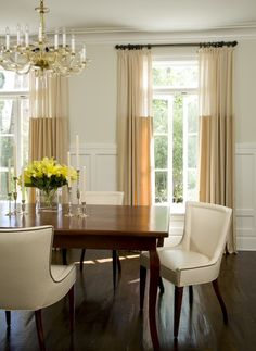Lighter fabric at the top (banded drapery panels). The panels in this elegant dining room are done in 1/3 ivory and 2/3 taupe lightweight fabric. When the draperies are closed, light filters through the gauzy panels, with more brightness at the top. Lightweight fabrics and rings add casualness to an otherwise formal looking space. by William Hefner Architecture Interiors & Landscape